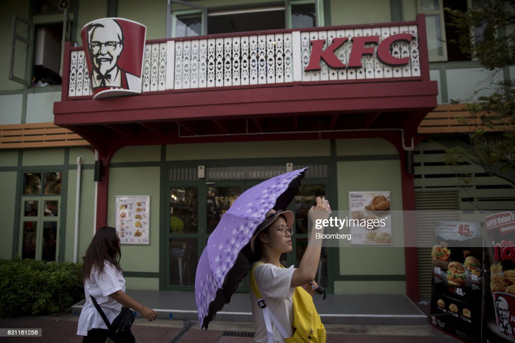 A woman holding an umbrella takes a photograph with a smartphone in front of a Yum! Brands Inc. KFC restaurant in Bangkok, Thailand, on Saturday, Aug. 12, 2017. Thai Beverage, the spirits giant that makes Chang beer and SangSom rum, is expanding into the fast-food business to take advantage of the rising appetite for fried chicken in Asia. ThaiBev agreed to purchase more than 240 existing KFC restaurants in Thailand for about 11.3 billion Thai baht ($340 million). Photographer: Brent Lewin/Bloomberg via Getty Images