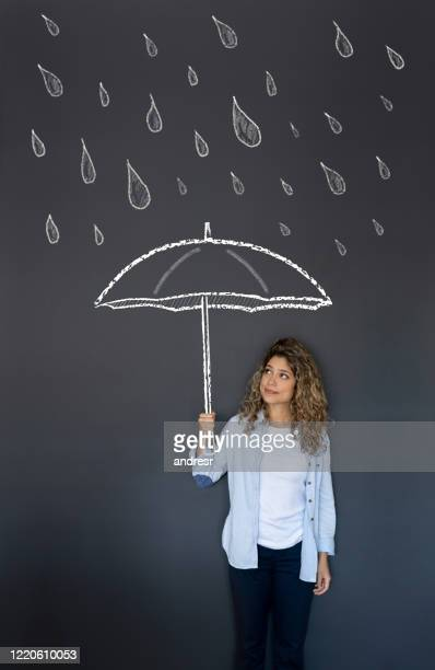 woman holding an umbrella under the rain - blackboard visual aid stock pictures, royalty-free photos & images