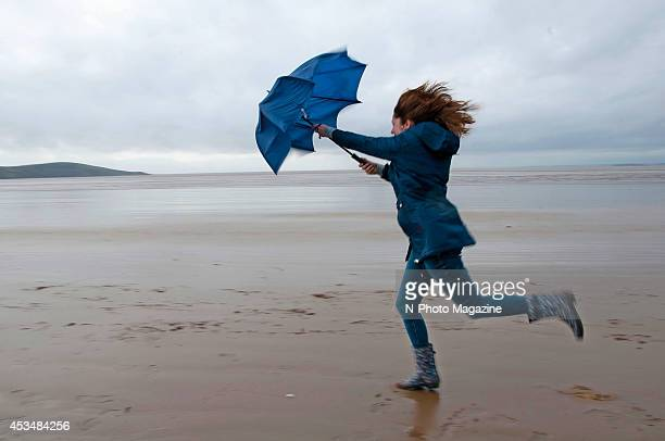 A woman holding an umbrella up against the wind on the beach at WestonsuperMare on October 21 2013