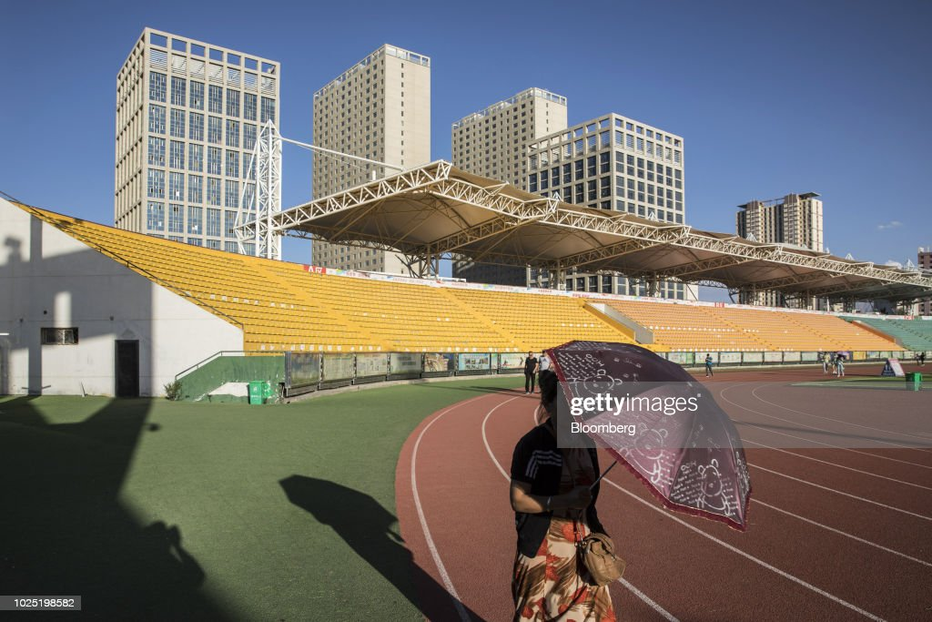 A woman holding an umbrella walks along a running track at a sports stadium as buildings stand in the background in Golmud, Qinghai province, China, on Monday, July 23, 2018. Amid rising fears about a trade war, China's policy makers have unveiled measures to boost infrastructure construction and credit to smaller firms, as well as tax cuts. Photographer: Qilai Shen/Bloomberg via Getty Images