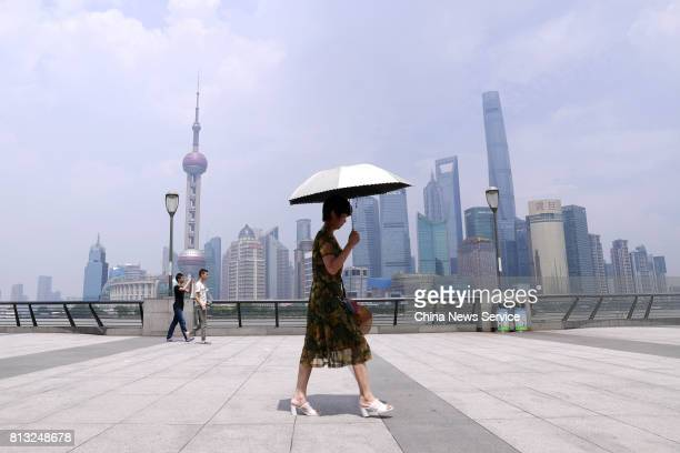 A woman holding an umbrella walks at The Bund on July 12 2017 in Shanghai China The dog days of summer start from July 12 in China Shanghai released...