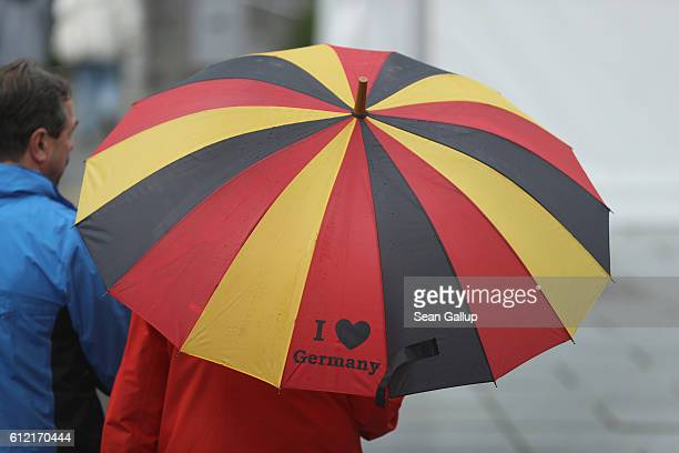 A woman holding an umbrella with the colors of the German flag walks to join a march by supporters of the Pegida movement on German Unity Day on...