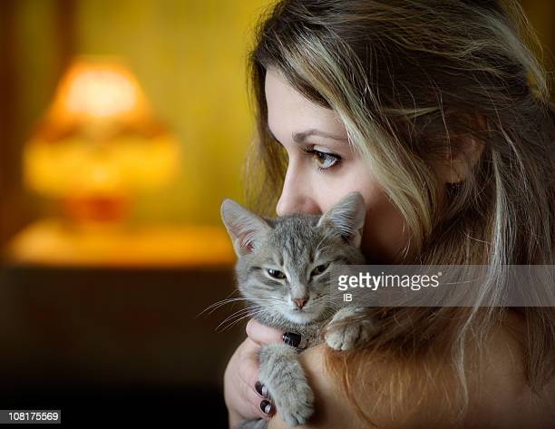 woman holding and cuddling kitten - petite teen girl stock photos and pictures