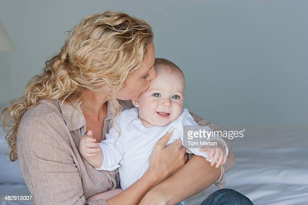 Woman holding and kissing baby on bed