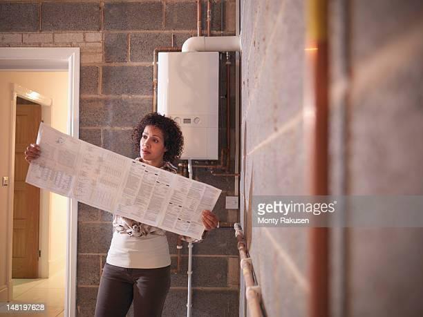 woman holding and reading instructions to energy efficient boiler - instruções - fotografias e filmes do acervo