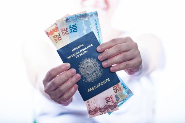 woman holding and showing the Brazilian passport with a lot of brazilian real money inside