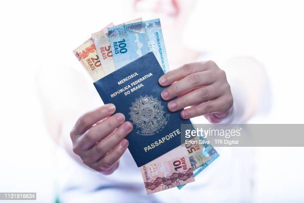 woman holding and showing the brazilian passport with a lot of brazilian real money inside - mão stock photos and pictures