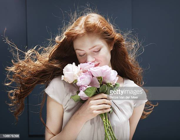 Woman holding and smelling bunch of roses