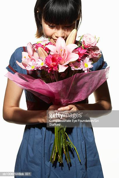 "woman holding and smelling large bouquet of flowers - ""compassionate eye"" stock pictures, royalty-free photos & images"