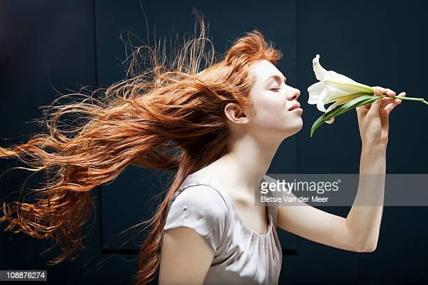 woman holding and smelling lily. - só uma mulher jovem imagens e fotografias de stock