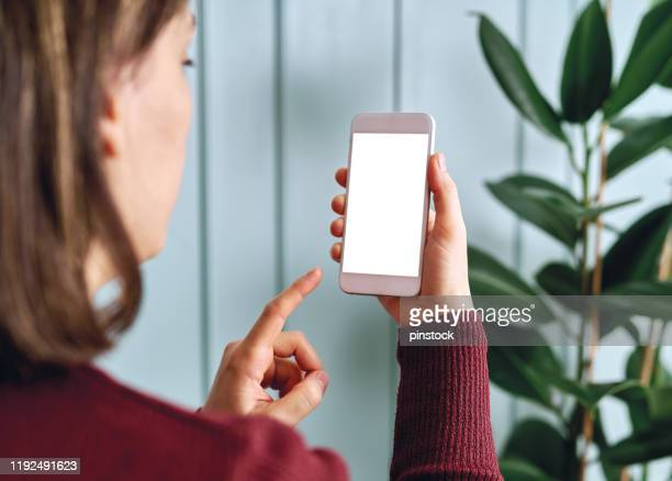 woman holding and touching blank screen template smart phone. smart phone screen is empty with clipping path. - iphone screen stock pictures, royalty-free photos & images