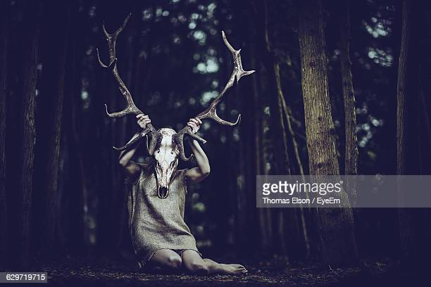 Woman Holding Antler In Forest
