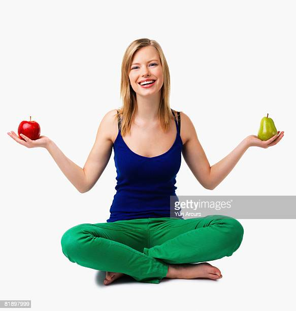 Woman holding apple and pear in hands