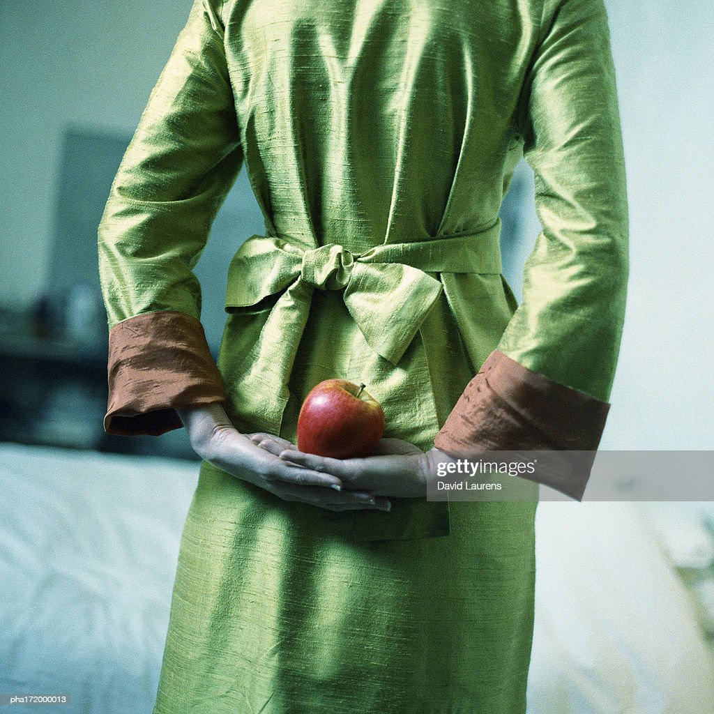 Woman holding apple behind back, mid-section, rear view : Stockfoto
