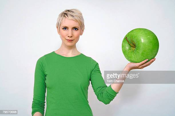 'Woman holding apple, close-up'