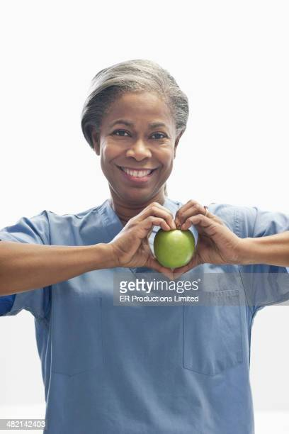 Woman holding apple in heart-shape