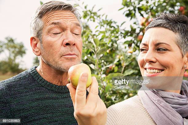 Woman holding apple out for man in orchard