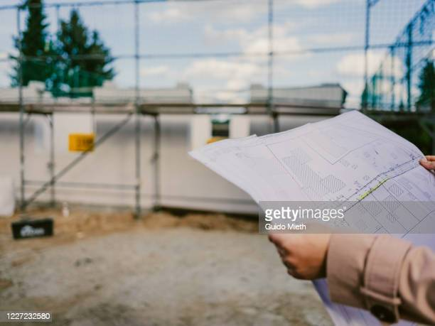 woman holding architect's plan of construction site. - baugewerbe stock-fotos und bilder