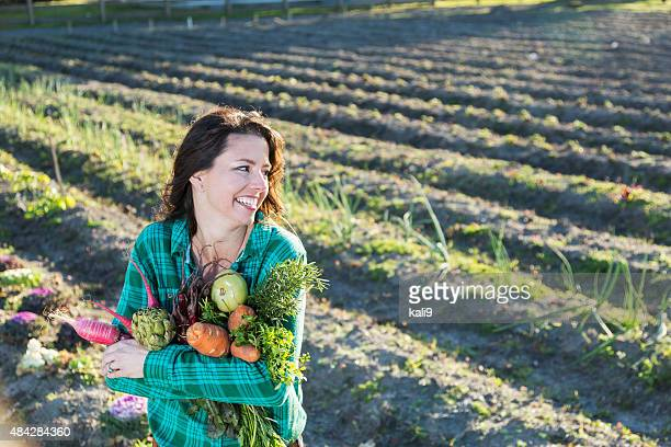 Woman holding armful of vegetables at organic farm