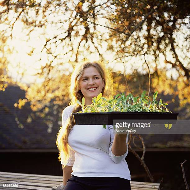 Woman holding artichoke plants