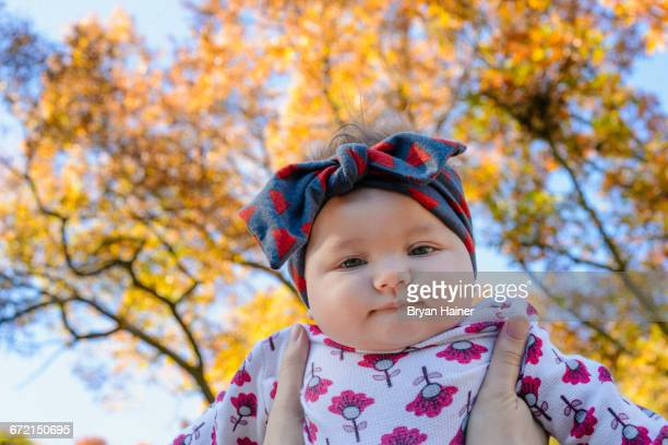 Woman holding baby girl against autumn tree