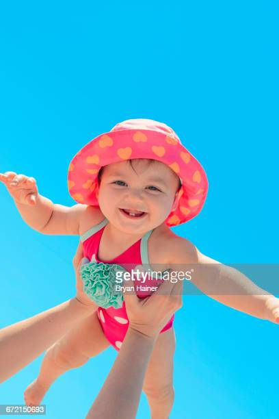 Woman holding baby girl against blue sky