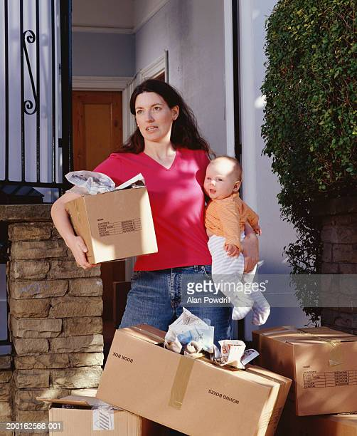 Woman holding baby girl (0-3 months) and removal box by front door
