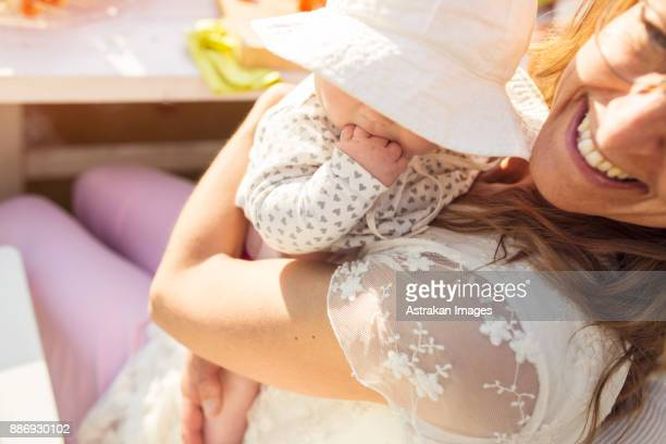 Woman holding baby girl (2-5 months) at garden party