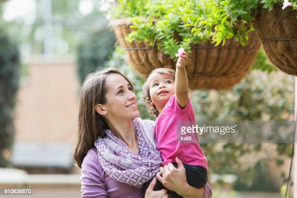 woman holding baby girl, reaching for flower - hanging basket stock pictures, royalty-free photos & images