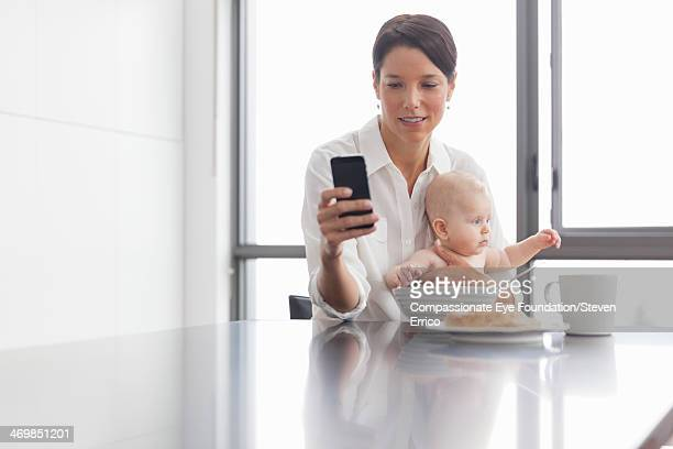 Woman holding baby in kitchen using mobile phone