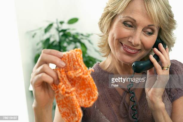 Woman Holding Baby Mittens While on Phone