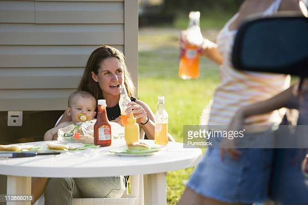 Woman holding baby sitting at picnic table