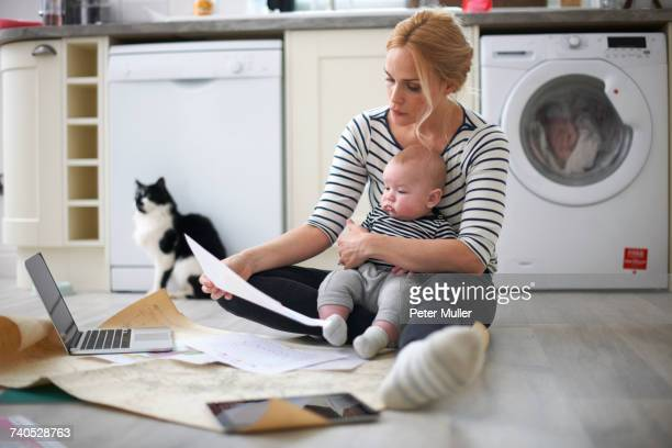 woman holding baby son in arms, looking through work on kitchen floor, laptop and digital tablet in front of her - multi tasking stock pictures, royalty-free photos & images