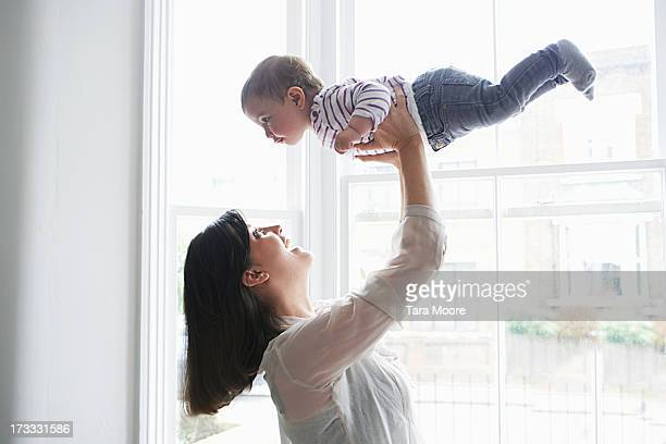 woman holding baby up in air in house
