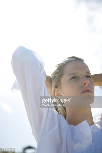 Woman holding back hair, low angle view