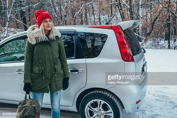 Woman holding backpack while standing by car on field