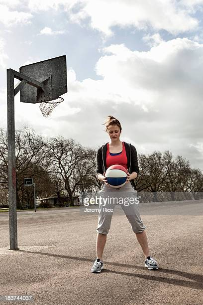 Woman holding ball at netball court