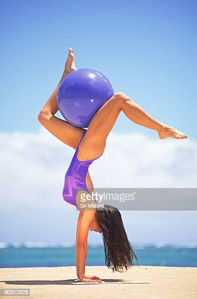 Woman holding ball between her legs