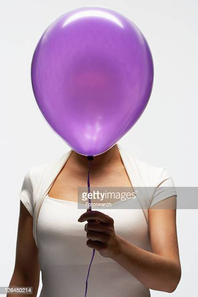 Woman holding balloon in front of her face