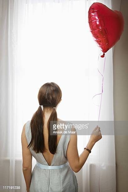 Woman holding balloon in front of window