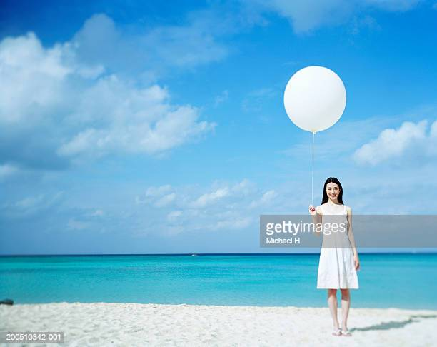 Woman holding balloon on beach, smiling, portrait
