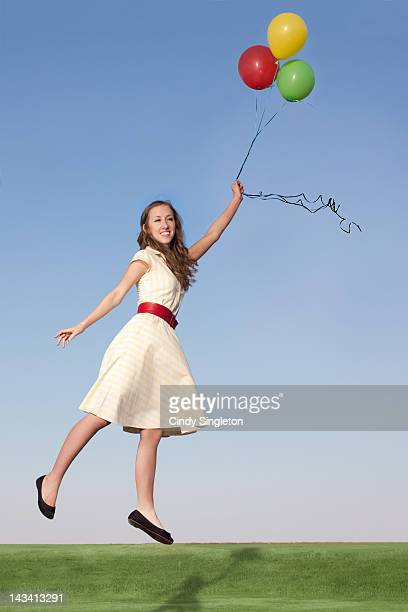Woman holding balloons and floating away