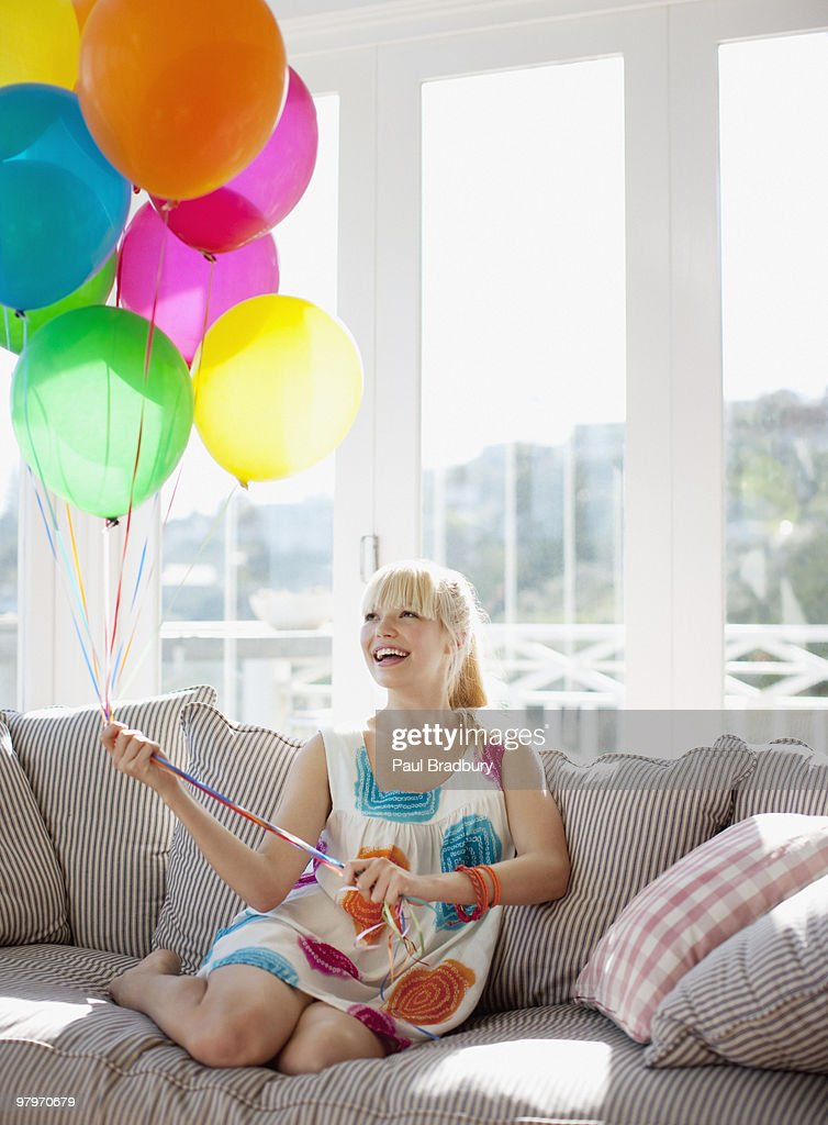 Woman holding balloons on sofa in living room : Stock Photo