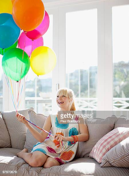 woman holding balloons on sofa in living room - birthday balloons stock photos and pictures