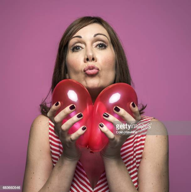 Woman holding balloons to make a heart shape