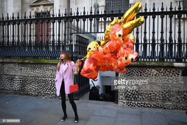 TOPSHOT A woman holding balloons waits before taking part a parade to celebrate the Chinese Lunar New Year in central London on February 18 2018 The...