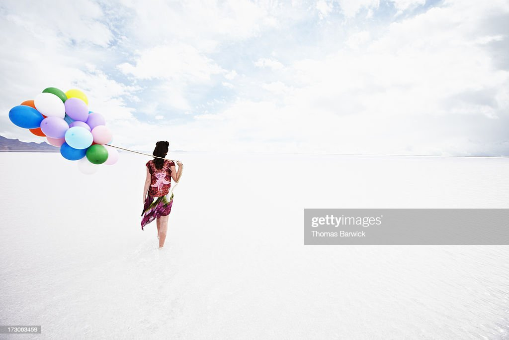 Woman holding balloons walking through water : Stock Photo