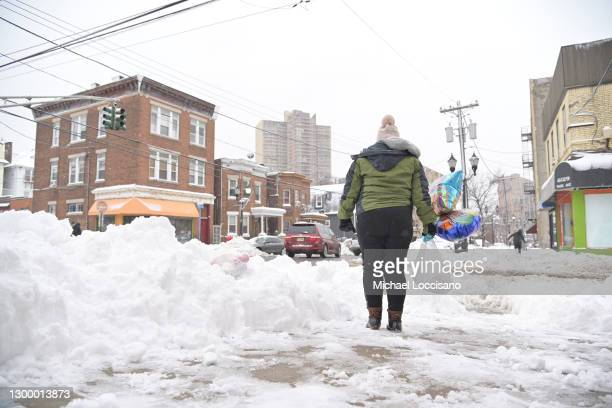 Woman holding baloons waits to cross the street on February 02, 2021 in West New York, New Jersey. Over two days of snow has covered some parts of...