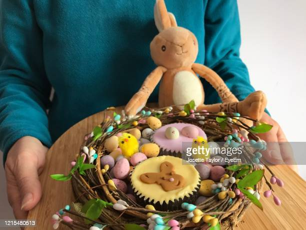 woman holding  bamboo board with iced cupcakes and chocolate easter eggs in a decorative nest shape. - easter sunday stock pictures, royalty-free photos & images