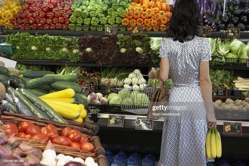 Woman holding bananas in produce aisle of supermarket, rear view : Stock Photo